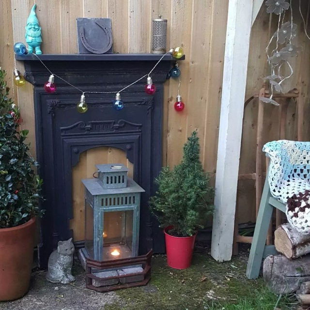 small fake fireplace outside with lantern on the ground photo by Instagram user @katysclutter
