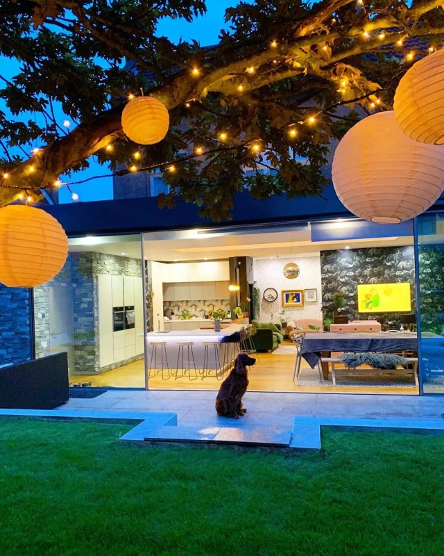 paper lanterns hanging from tree in backyard with dog in view photo by Instagram user @comedowntothewoods