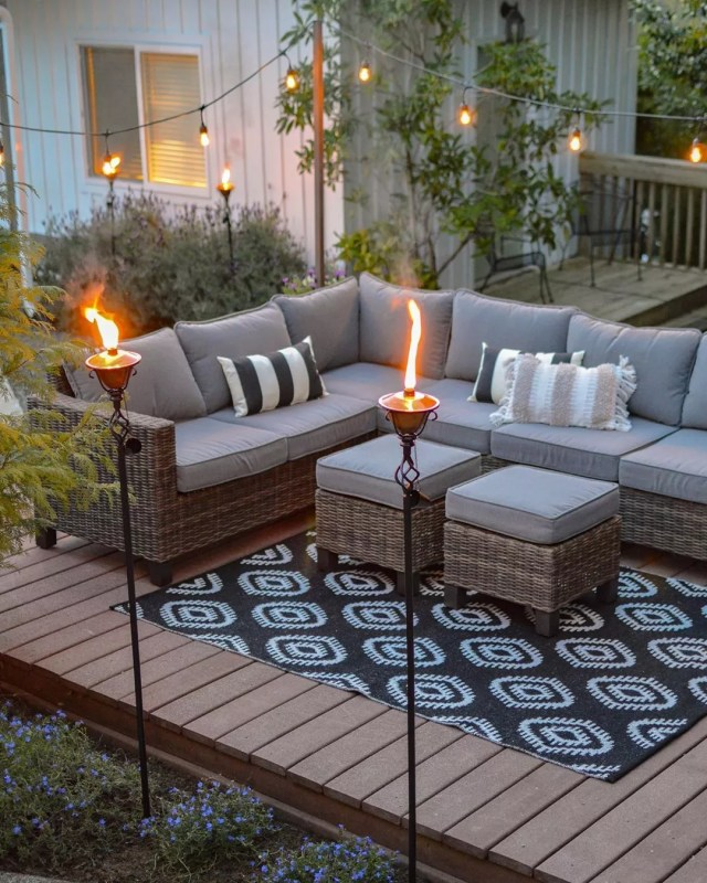 tiki torches set up around the outdoor patio and furniture photo by Instagram user @foxhollowcottage