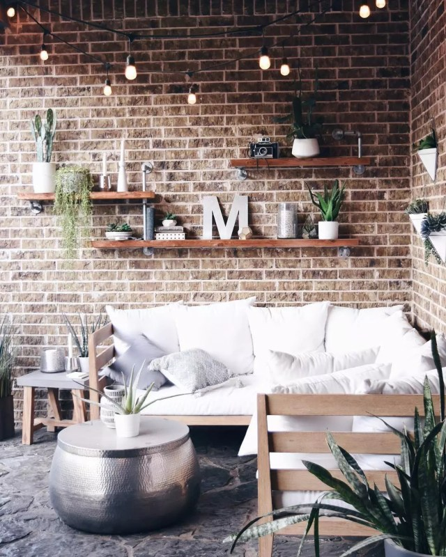 outdoor seating area with floating shelves set up on brick wall photo by Instagram user @pillowthoughthome
