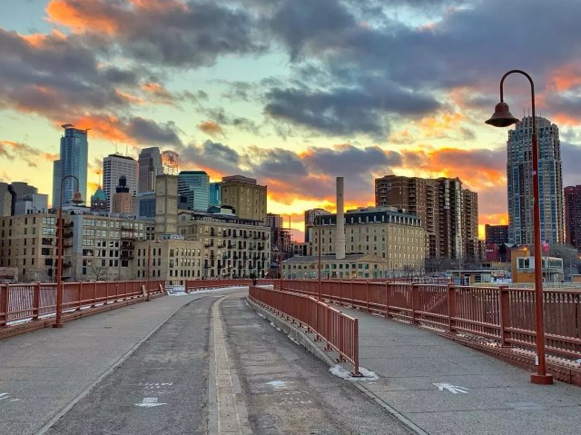 Minneapolis downtown skyline at dusk from stone bridge pathway photo by Instagram user @lobaby42