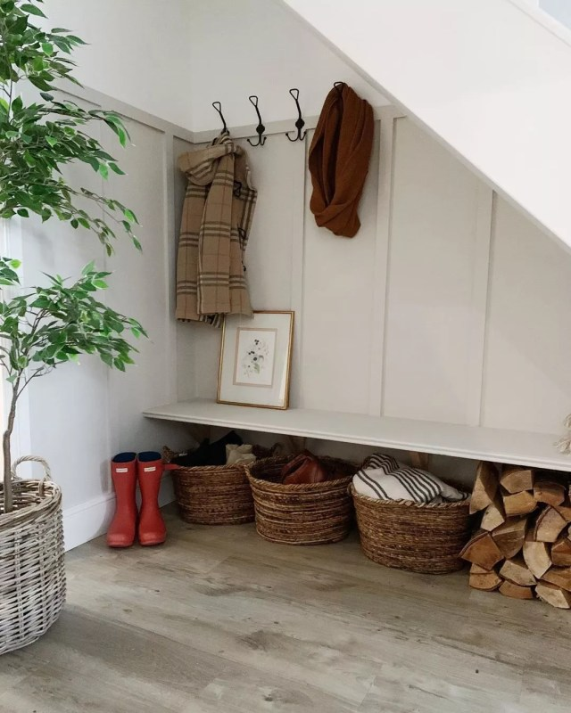 small mud room with coat hangers and a bench with wicker baskets underneath photo by Instagram user @my_best_laid_plans