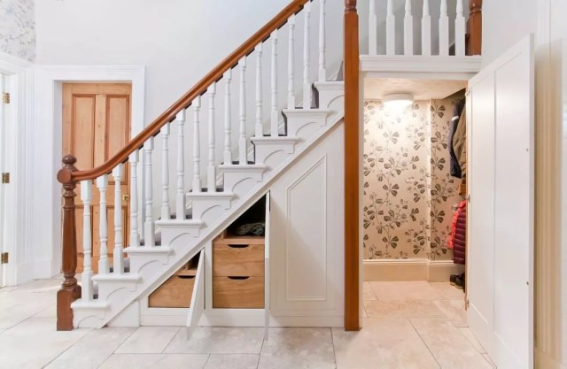 under stairs closet with coats hanging up and smaller cabinets photo by Instagram user @watkinson_cabinet_makers