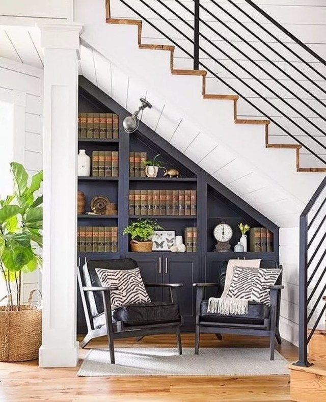 small library made under home stairs with two chairs and a spotlight photo by Instagram user @allusterstorage