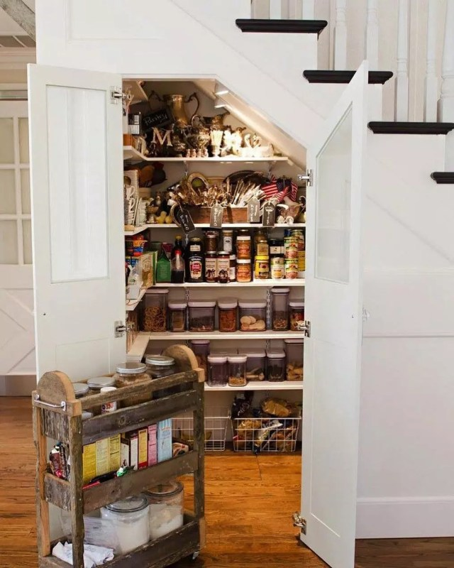 kitchen pantry with rolling cart under the stairs photo by Instagram user @mikerobertshomes
