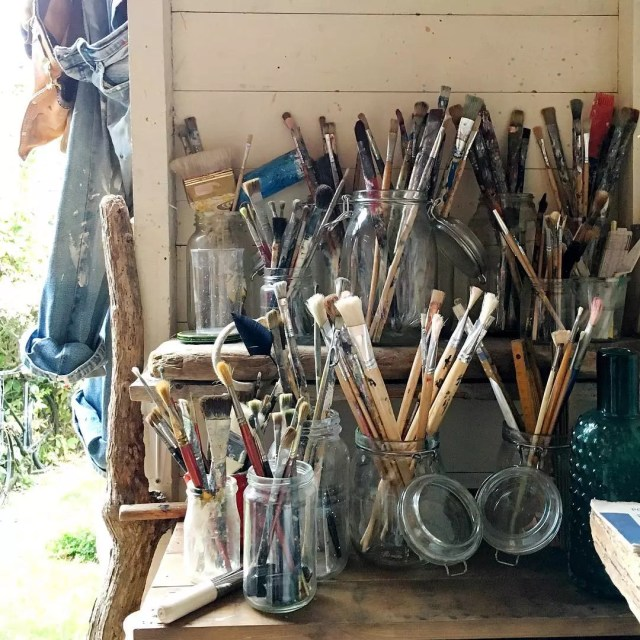 extra paint brushes being stored in old mason jars photo by Instagram user @silverpebble2