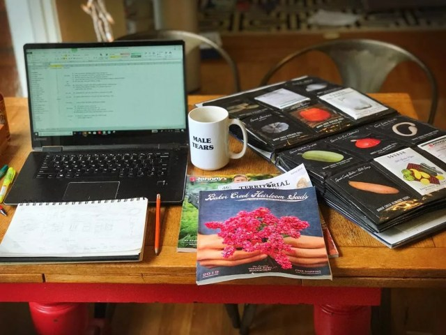 work station organizing vegetable seeds in photo album photo by Instagram user @organicallygrowing