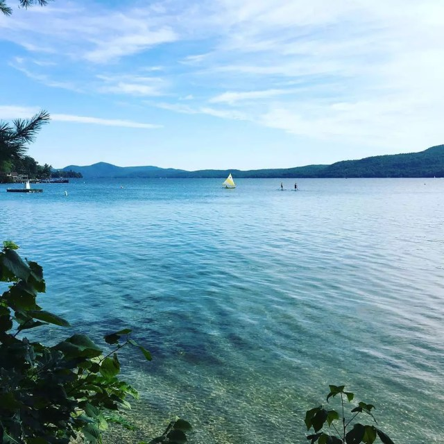 Sailboat and People Using Paddleboards on Lake George in New York. Photo by Instagram user @lakegeorge_ny