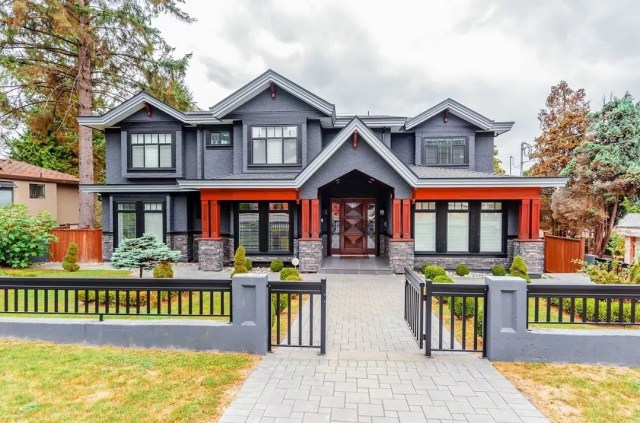 Front view of unique two-story single-family home with dark blue siding and red accents. Photo by Instagram user @steelrhinoinspections