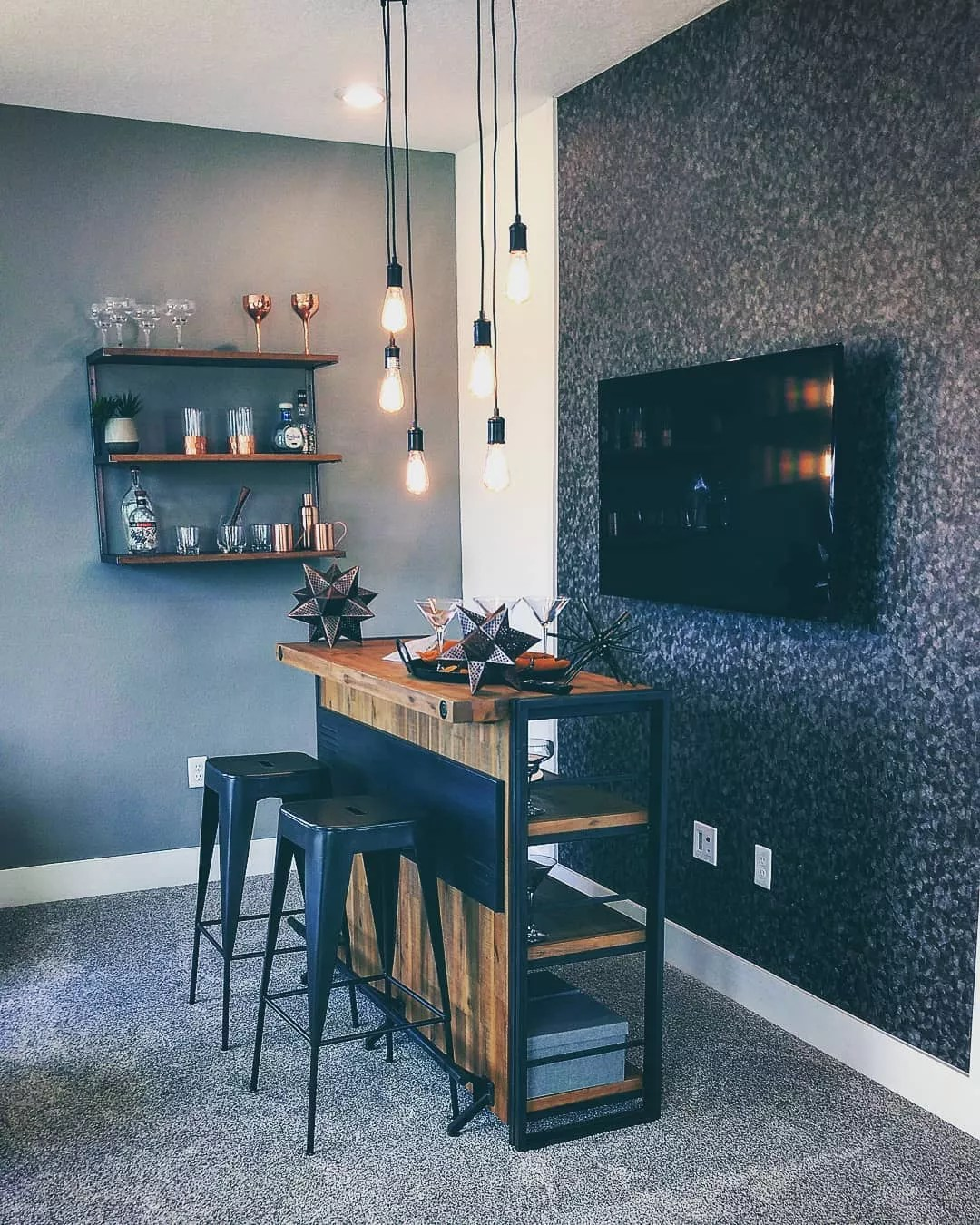small bar with tv behind it and glasses set up on shelves on the wall photo by Instagram user @nikki.rittenberry_realtor