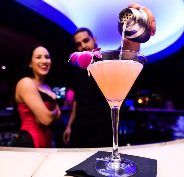 Bartender pouring a fruity martini with woman standing next to him. Photo by Instagram user @bluemartinilounge
