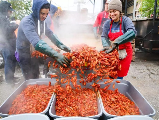 Two people throw crawfish into bins for patrons to eat at Rajun Cajun Crawfish Festival. Photo by Instagram user @frankchinmemphis