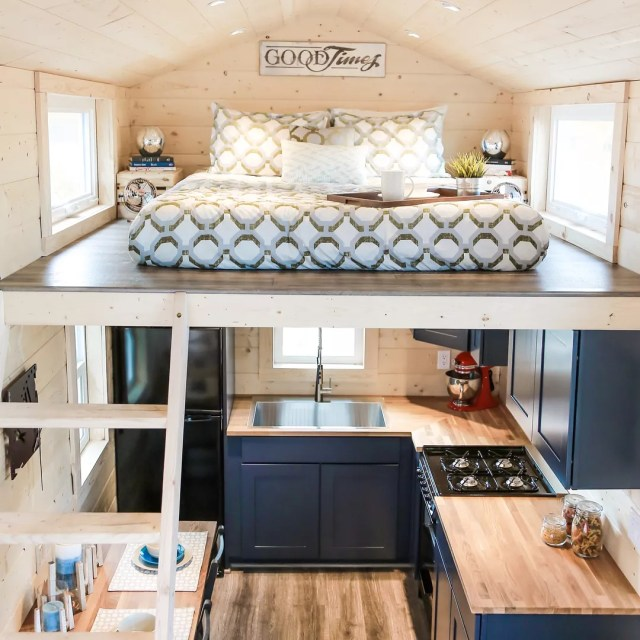 Tiny home with bed lofted above kitchen. Photo by Instagram user @unchartedtinyhomes