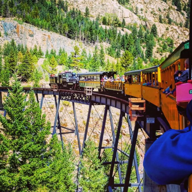 Passenger Train Moving Along Elevated Tracks Through the Rocky Mountains. Photo by Instagram user @xmolinavalos