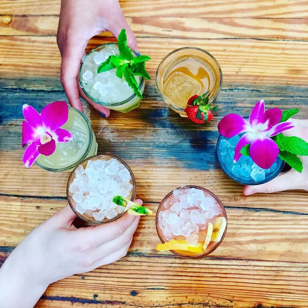 Overhead View of Six Different Alcoholic Drinks with Flowers and Herbs on Top. Photo by Instagram user @roofatparksouth