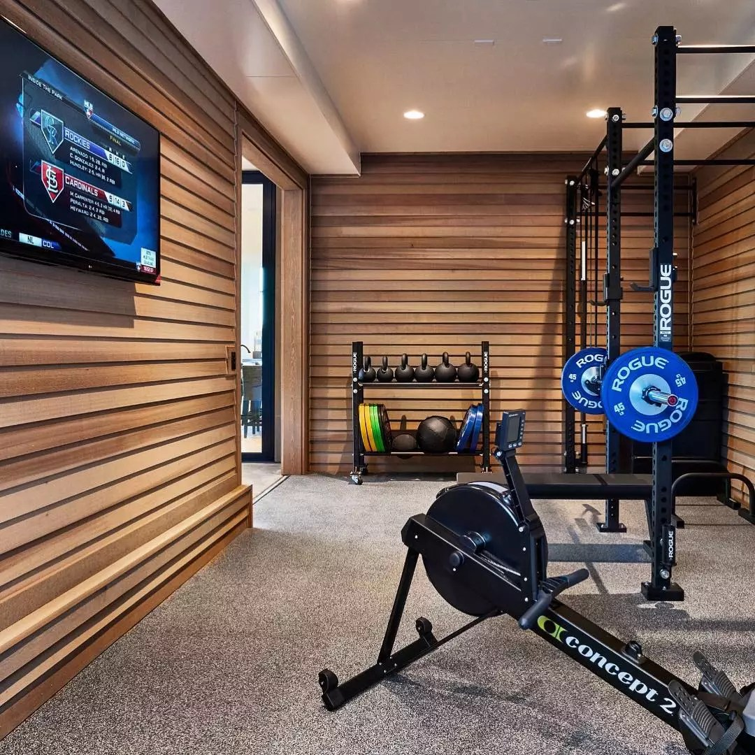 Home fitness room with weights, rowing machine, and TV. Photo by Instagram user @ajestudio