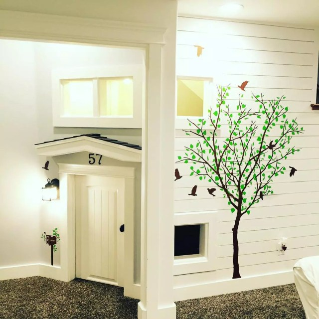 White playhouse with painted tree under stairs. Photo by Instagram user @design_by_desiree