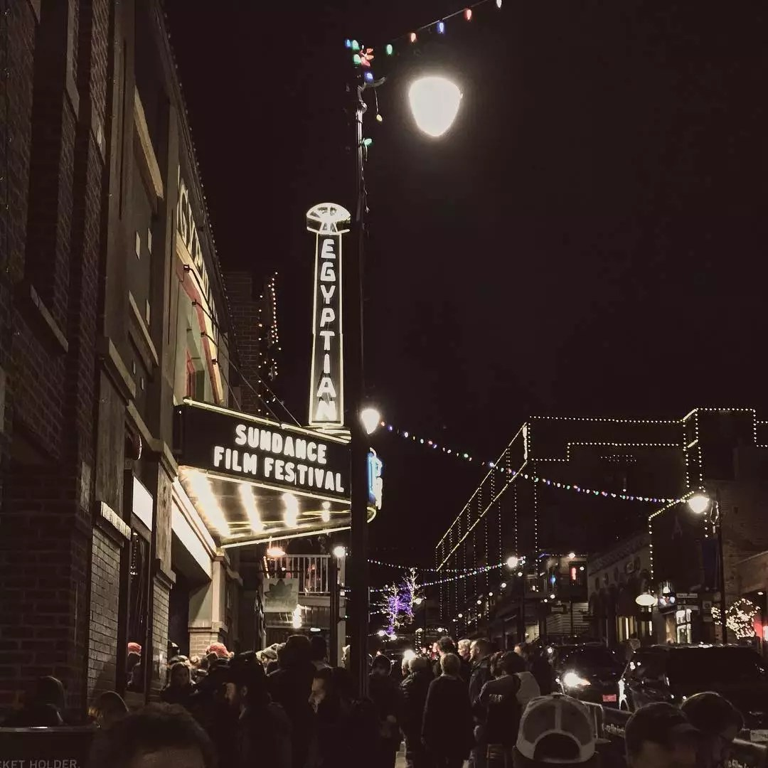 A crowd of people stand outside a theater as the signs for Sundance Film Festival light up above. Photo by Instagram user @sundanceorg