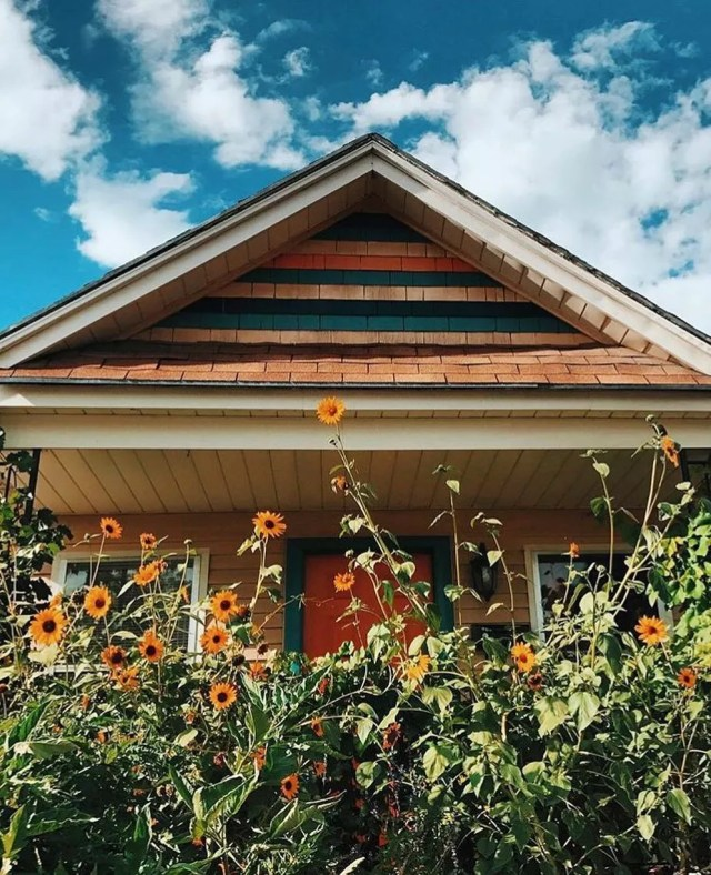 Old cottage style home with tall sunflowers growing in front of the porch. Photo by Instagram user @nikkiboliaux