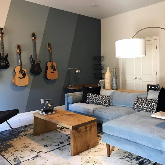 home music room with large sectional couch and guitars on the wall photo by Instagram user @houseliftdesign