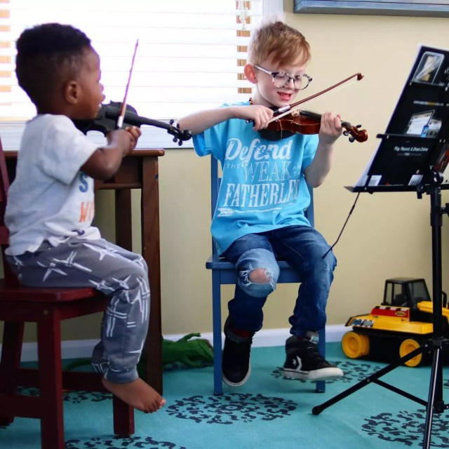 two young kids playing violins in a small music room photo by Instagram user @amymlantz