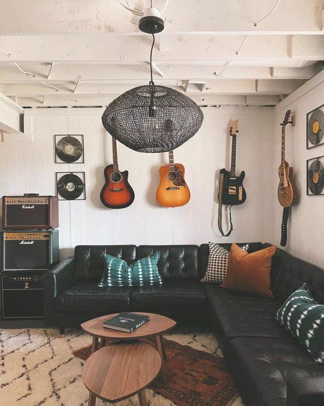 music room in home set up with large seating area and instruments on the wall photo by Instagram user @designandcaroline