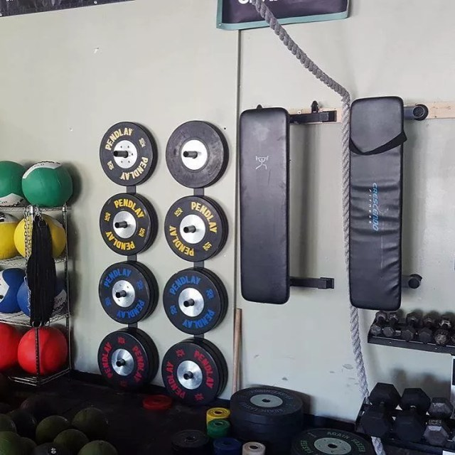 Barbell weights and benches hung from wall in gym. Photo by Instagram user @bullcitystrong