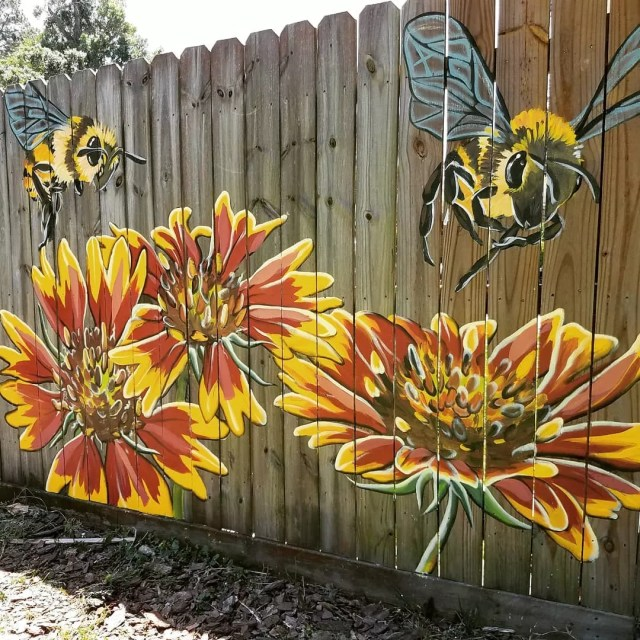 Red and yellow flowers and a bee fence mural. Photo by Instagram user @bettysmith.art