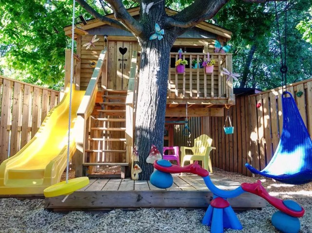 Tree house swing set with yellow slide. Photo by Instagram user @marc_d_porkchop