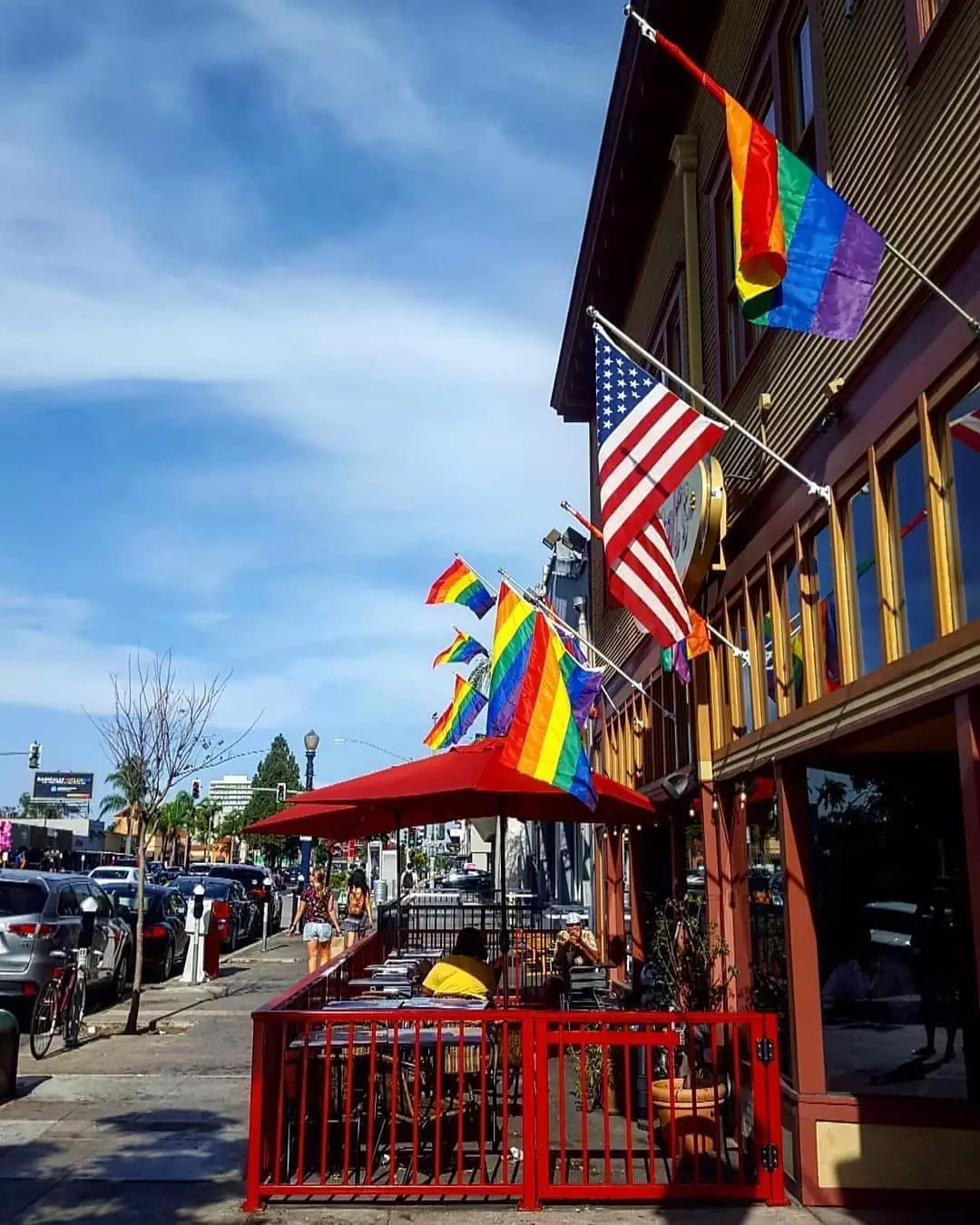 PRIDE flags flying beside a United States glad above the seating area of a sidewalk cafe. Photo by Instagram user @nowtrendingapp