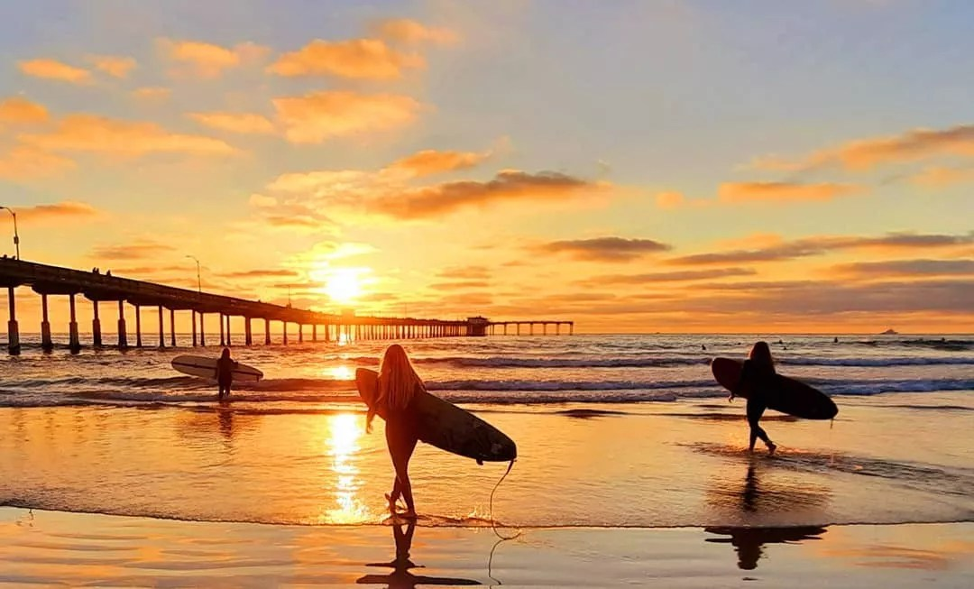 Women Walking into the Ocean with Surfboards Next to the Ocean Beach Pier. Photo by Instagram user @barryalman
