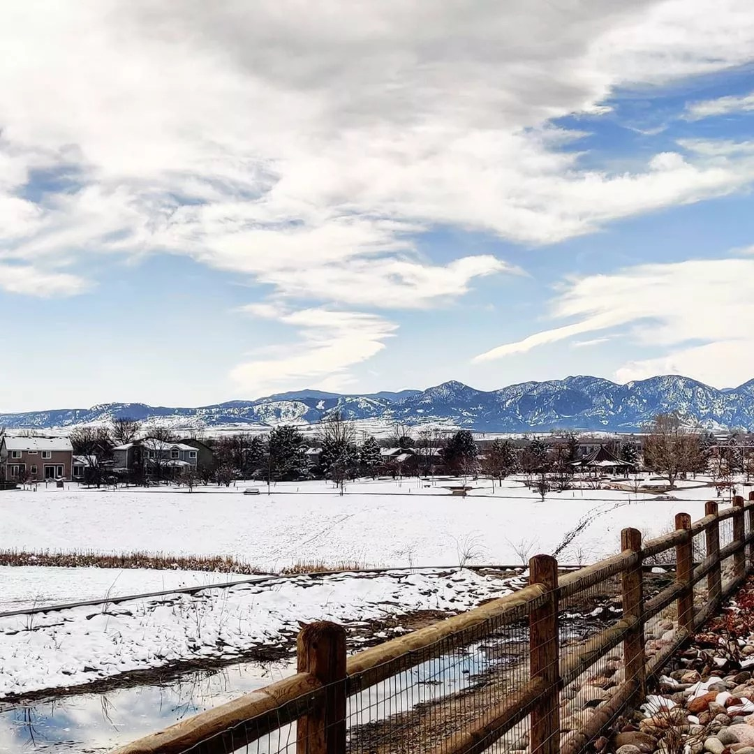 snow covered field with wood post fence with mountains in background photo by Instagram user @whalekisser