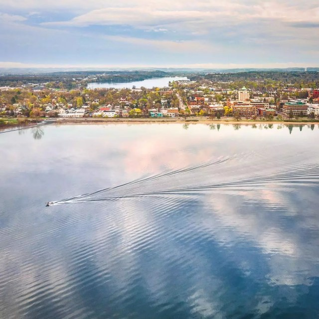 traverse city lake with boat on the water and town in view photo by Instagram user @tonydemin