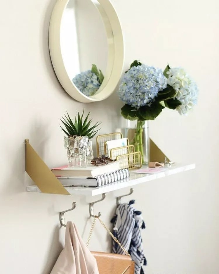 Floating shelf with hooks and mirror in apartment entryway. Photo by Instagram user @@medallion_corp