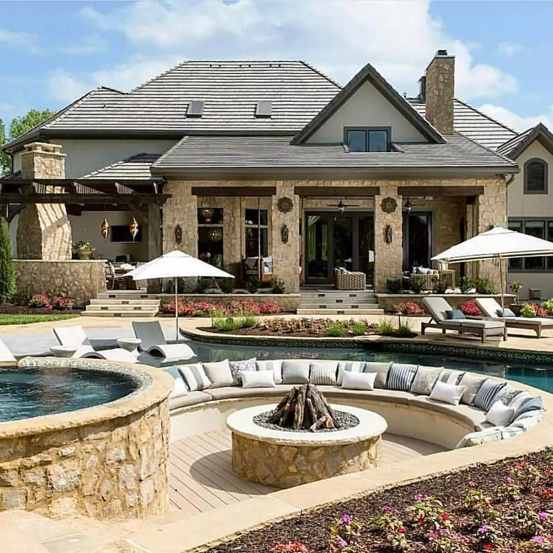 Fire pit attached to an outdoor pool and hot tub. Photo by Instagram user @starrsellshomes