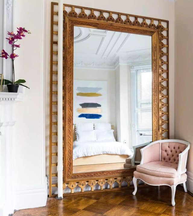 large mirror in bedroom to extend the room with pink chair next to it photo by Instagram user @apartmenttherapy