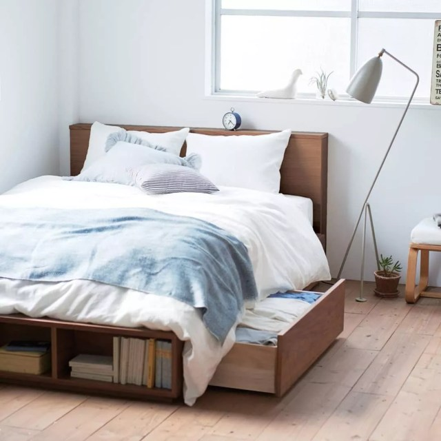 Platform bed with storage drawers in minimalist apartment. Photo by Instagram user @mujigermany