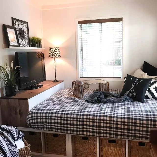 Studio apartment bed with footboard for TV storage. Photo by Instagram user @urbancottageliving