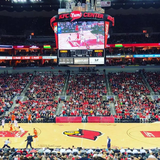 Looking down at the center Louisville basketball court and jumbotron during game. Photo by Instagram user @brigidkaelin