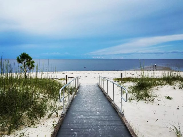 View of the ocean and white sand from path leading to beach. Photo by Instagram user @theexplorerchick