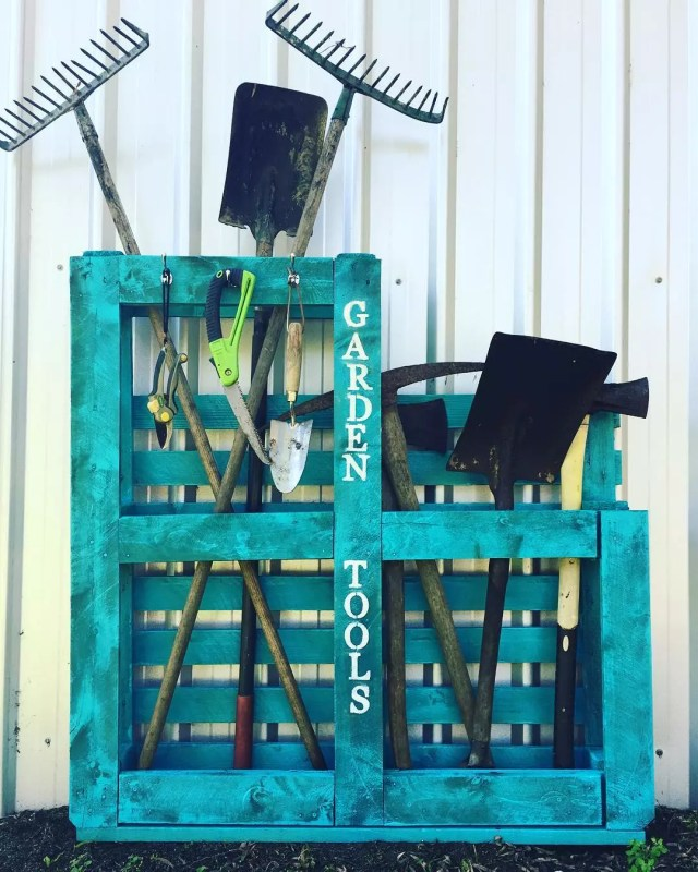 Blue wooden pallets holding garden tools. Photo by Instagram user @inspire.furniture