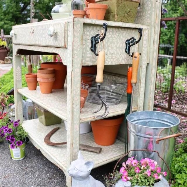 Repainted dresser outside with pots and rakes on it. Photo by Instagram user @cuttingedgestencils