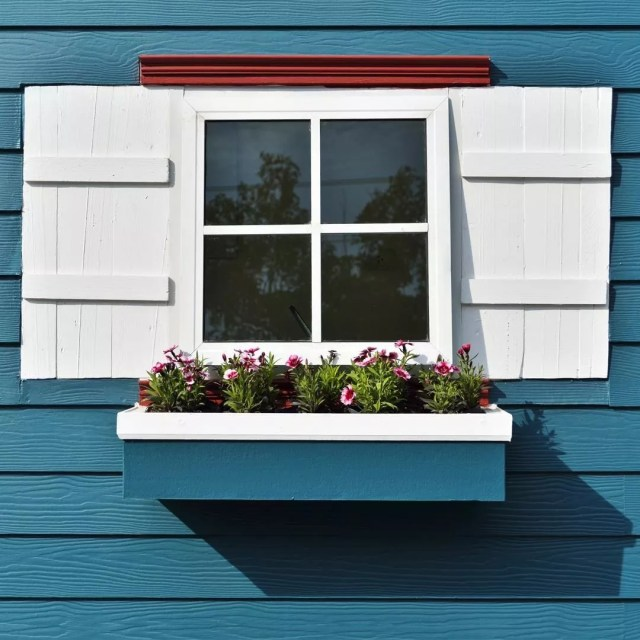 Window boxes outside blue house. Photo by Instagram user @nationalhrdware