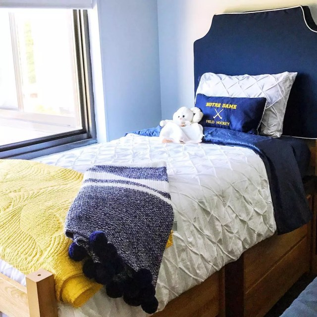 College Dorm Room Bed with Blue & Yellow Throw Blankets. Photo by Instagram user @fourteenth_floor