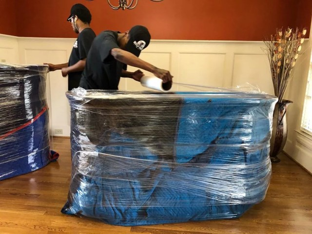 Man Wrapping a Large Dresser in Plastic Wrap for Moving. Photo by Instagram user @wolfpackmovers