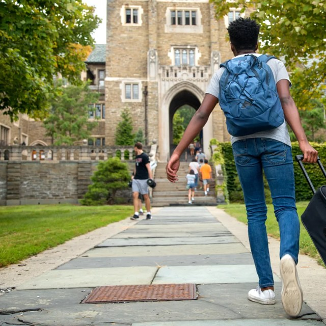 College Student Wheeling Bag onto College Campus. Photo by Instagram user @cornelluniversity
