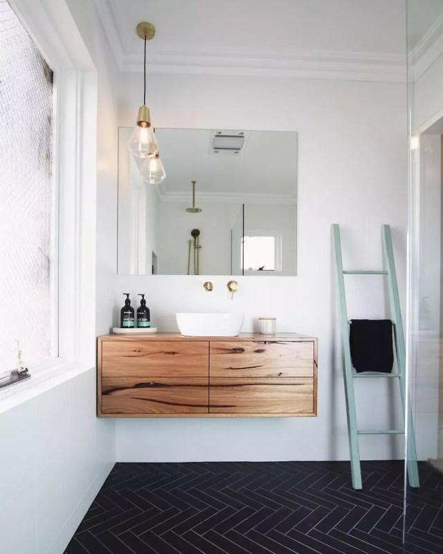 floating vanity in bathroom with black tile floors photo by Instagram user @timberwolf_design