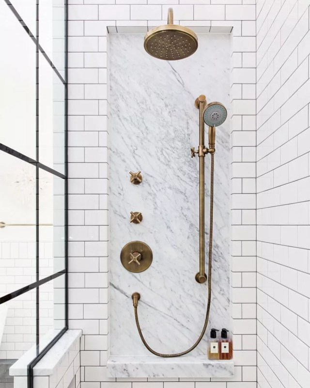 white tile shower with multiple gold shower heads photo by Instagram user @alannadunn