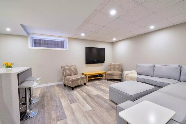 basement with couch and chairs with drop ceilings and recessed lighting photo by Instagram user @grindstonerenos