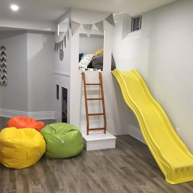 kids play area with yellow slide and bean bags in basement photo by Instagram user @contractingbyus
